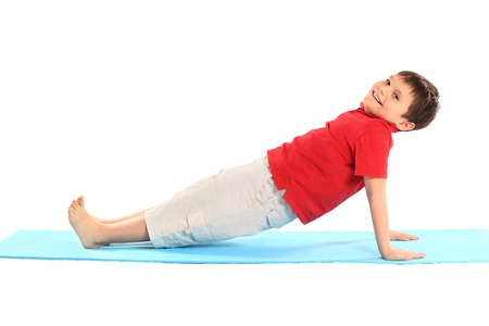 Childrens yoga. The little boy does exercise. 版權商用圖片