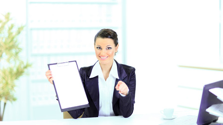 Beautiful business woman in the office, at the work place with the work plan. Stock Photo - 25395799