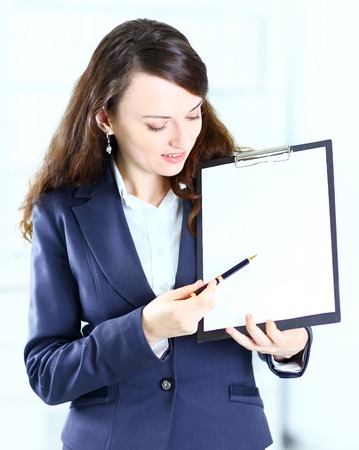 Portrait of a cute young business woman with the work plan smiling. Stock Photo - 25759936