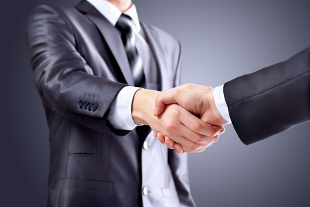 Photo of handshake of business partners after signing promising contract