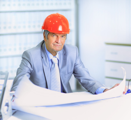 corrects: Engineer at the age of considering plans drawing and corrects them. Stock Photo