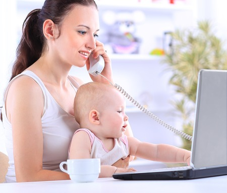 old home office: Mother and baby in home office with laptop and telephone
