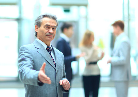 Welcoming business man ready to handshake with hand extended  photo