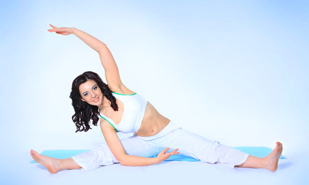 pretty brunette in white active wear on white background photo