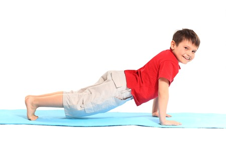 Childrens yoga. The little boy does exercise. Imagens