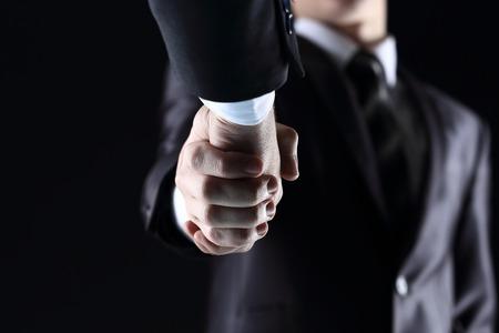 Handshake - Hand holding on dark background Standard-Bild
