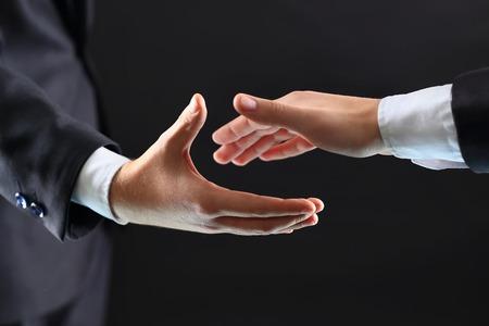 Photo of hands of business partners before handshake in black background Standard-Bild