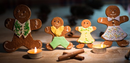 Christmas gingerbread men candles with cinnamon stars Pine twig Christmas ball on a wooden floor photo