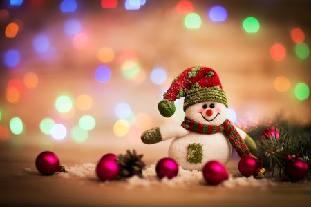 Christmas background with Christmas tree and snowman on a rustic wooden board Standard-Bild