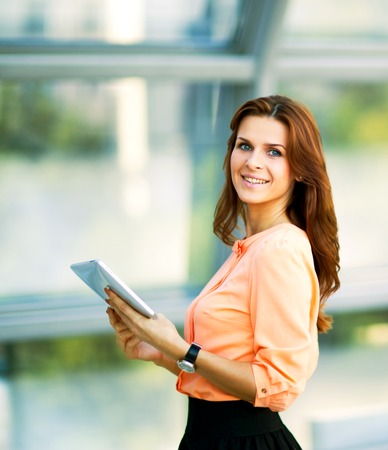 Young smiling business woman holding digital tablet computer