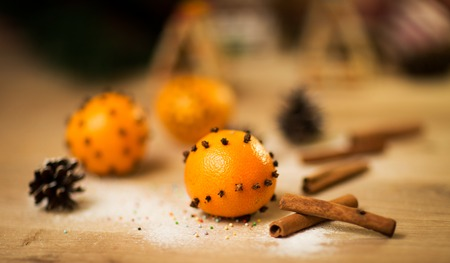New year decoration tangerines with cinnamon on wooden table photo