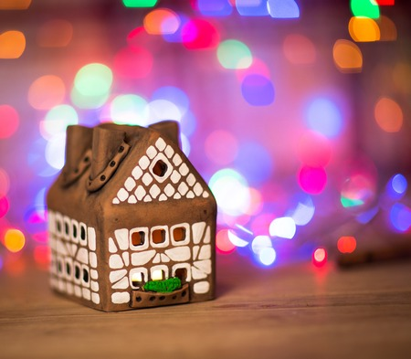 narrow depth of field: fairy Christmas house cake with candle light inside, narrow depth of field and background lights
