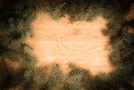 bedeck: green fir branches on the wooden floor with darkening at the edges