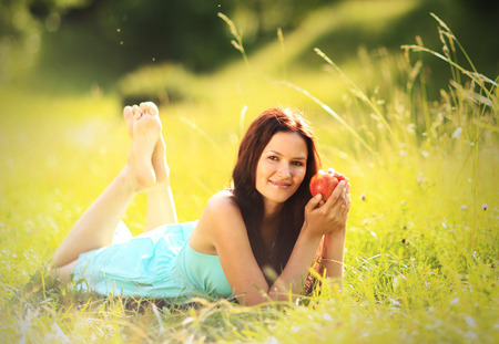 Beautiful woman with apple outdoor photo