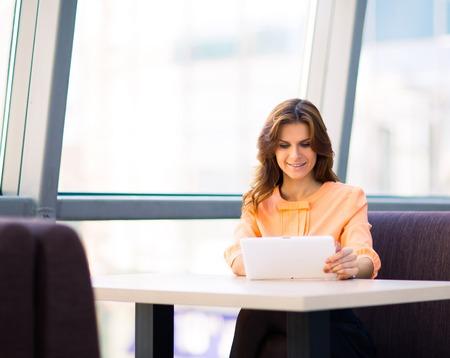 Jeune femme d'affaires souriant tenant ordinateur tablette numérique la table