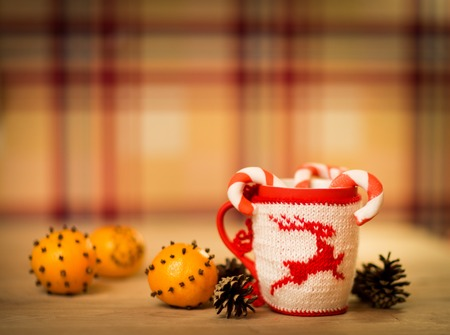 insulated wool cloth mug with embroidered deer on the wooden table mug with tangerines and a candy photo
