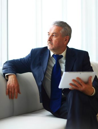businessman in office with the tablet sits and works photo