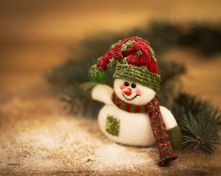 Christmas background with Christmas tree and snowman on a rustic wooden board photo
