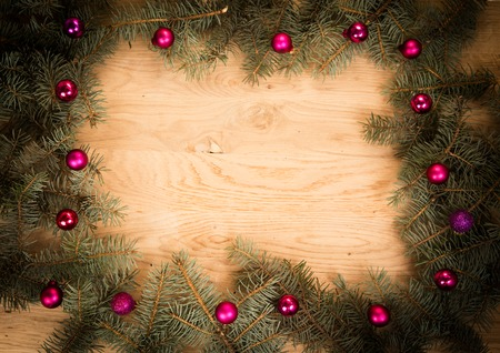 bedeck: green fir branches on the wooden floor with darkening at the edges with Christmas balls