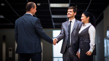 hand out: cheerful business men shaking hands
