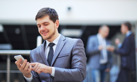 40 years old man: usinessman standing inside modern office building looking on a mobile phone Stock Photo