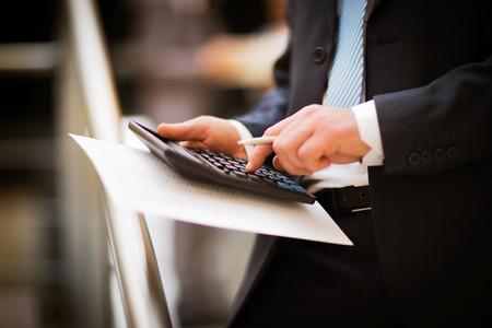 As mãos dos homens com calculadora. Cálculo no escritório