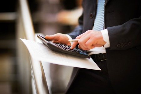 payroll: Mens hands with calculator. Calculation at office