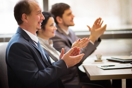 Close-up of business people clapping hands. Business seminar concept photo