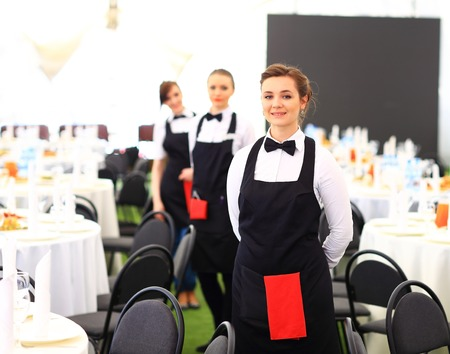 Large group of waiters and waitresses standing in row.