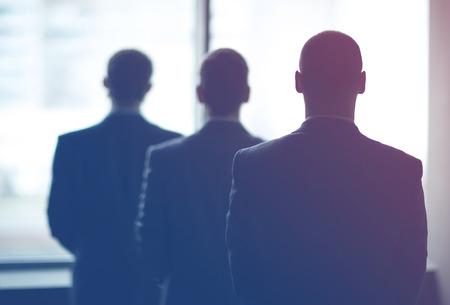 agent de sécurité: silhouette de trois hommes d'affaires dans le bureau