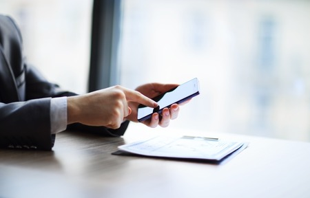 Close up of a man using mobile smart phone in office