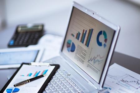 value: Negocios que analiza listas de inversi�n con el port�til. Contabilidad Foto de archivo
