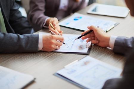 Diskussion über die Regelung. Seitenansicht von Geschäftsleuten und zeigte Griffe auf der Karte zusammen, die am Tisch sitzen Standard-Bild