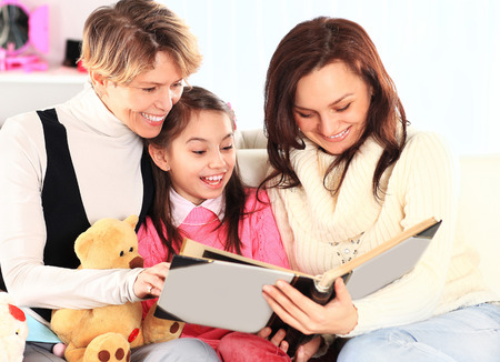 grandmother mother daughter: Grandmother, mother, and daughter reading a book together Stock Photo