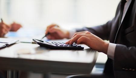 Business-Leute zählen auf Rechner am Tisch sitzen. Nahaufnahme von Händen und Schreibwaren Standard-Bild - 37580280