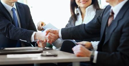 Mature Businessman Händeschütteln, einen deal mit seinem Partner und Kollegen in einem modernen Büro zu versiegeln Standard-Bild - 37580459