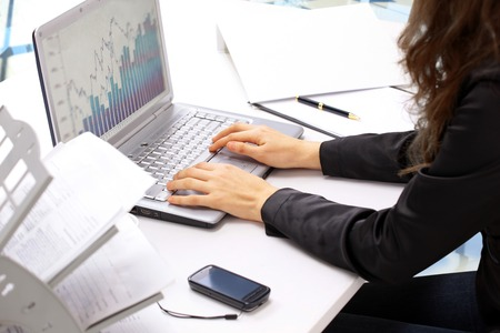 teclado de computadora: Manos femeninas que pulsan en el teclado y el rat�n mientras mantiene. El an�lisis de los gr�ficos de ventas.