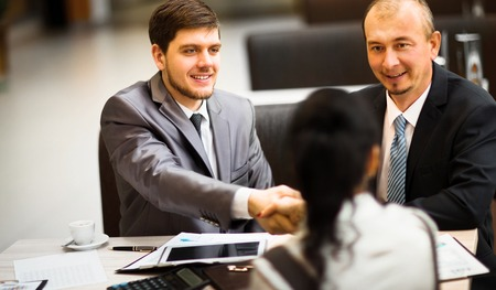 altogether: Business people shaking hands, finishing up a meeting Stock Photo