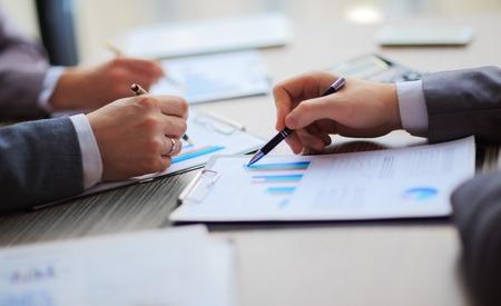 Diskussion über die Regelung. Seitenansicht von Geschäftsleuten und zeigte Griffe auf der Karte zusammen, die am Tisch sitzen Standard-Bild - 37754901