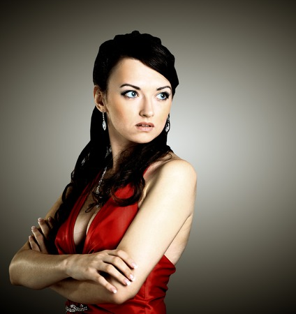 Woman with beauty long brown hair, red dress- posing at studio photo