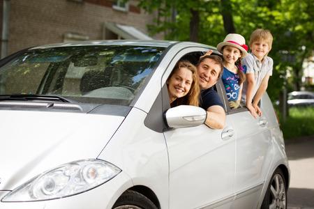 fiesta familiar: familia feliz en el coche que va en un picnic