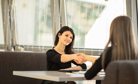people shaking hands: Two Businesswomen Shaking Hands In Modern Office
