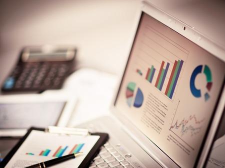 grafica de pastel: Negocios que analiza listas de inversión con el portátil. Contabilidad Foto de archivo