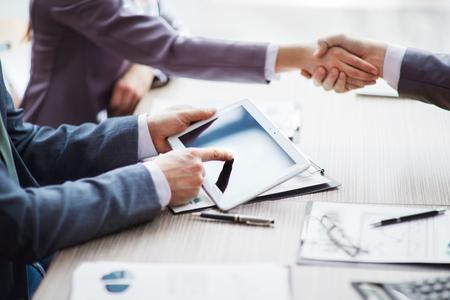 stretta di mano: Un gruppo di uomini d'affari discutere la politica della società in ufficio.