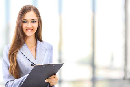 Portrait d'une jeune femme d'affaires joli sourire, dans un environnement de bureau
