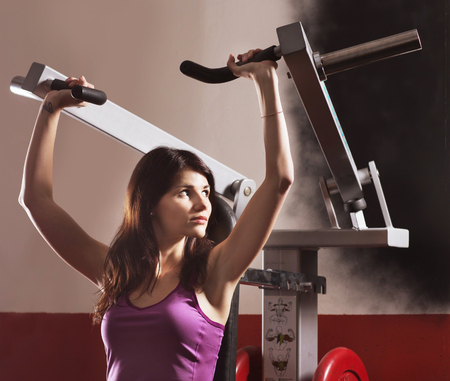 brawny: athletic girl , to do the exercises on a sports apparatus and a smile, in the sports hall