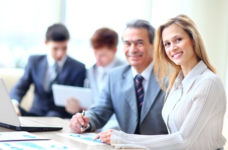 board room: Smiling business people with paper work in board room