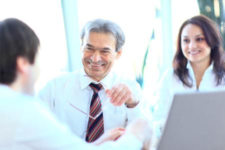 reunion de trabajo: Sonriendo gente de negocios con el papeleo en sala de juntas