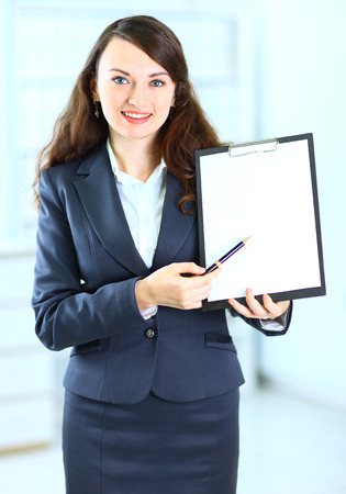 woman handle success: Portrait of a cute young business woman with the work plan smiling. Stock Photo