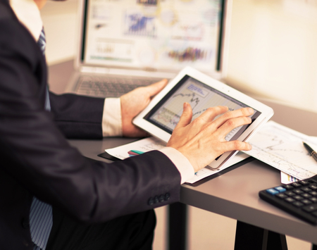 input device: Businessman with finger touching screen of a digital tablet Stock Photo